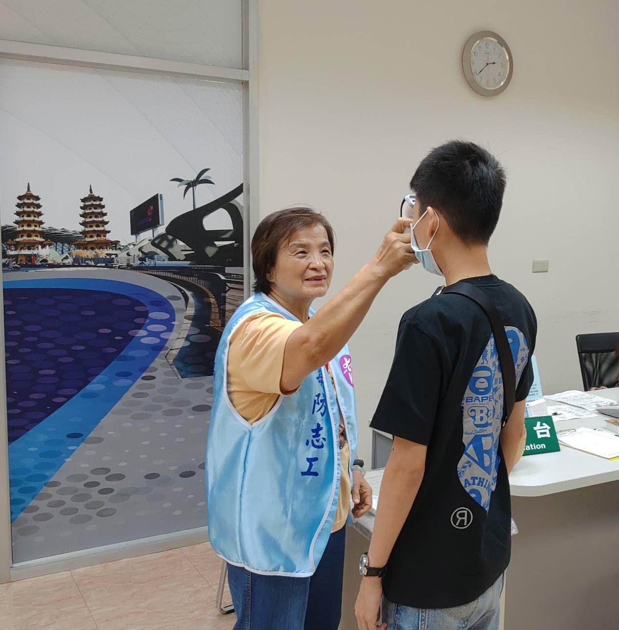 圖2-王鄭麗惠志工於毒防局服務台協助洽公民眾體溫測量,並友善引導。.jpg